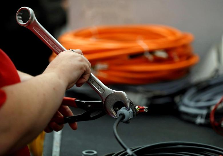 A worker attaches a connector to electrical wire on the factory floor of PP Control and Automation near Cannock, Britain, July 6, 2016.   REUTERS/Phil Noble/File Photo      GLOBAL BUSINESS WEEK AHEAD PACKAGE - SEARCH ''BUSINESS WEEK AHEAD AUG 1'' FOR ALL IMAGES - RTSKHR7