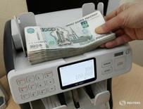 Кассир пересчитывает рублевые купюры в Красноярске 22 января 2016 года. Рубль дорожает утром понедельника в паре с долларом, отражая текущее снижение валюты США на форексе при возобновлении позитивной динамики нефтяных цен после их существенного пятничного роста. REUTERS/Ilya Naymushin