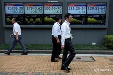 Пешеходы проходят мимо экрана с котировками у биржи в Токио 6 июля 2016 года. Ведущий фондовый индекс Японии Nikkei завершил сессию понедельника на максимуме более трех месяцев, хотя и растерял некоторую часть утреннего роста в условиях волатильных торгов, при этом акции банков подверглись распродаже после слов главы японского центробанка о готовности к дальнейшему смягчению денежно-кредитной политики. REUTERS/Issei Kato