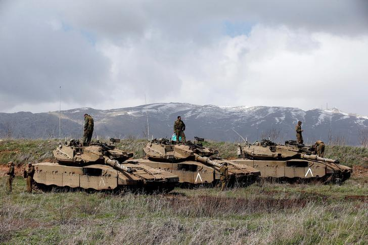 Israeli soldiers stand atop tanks in the Golan Heights near Israel's border with Syria March 19, 2014. REUTERS/Ronen Zvulun/Files