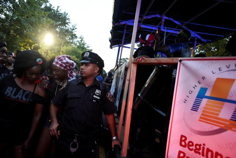 A New York City police officer guards a float participating in the overnight-into-dawn celebration called J'Ouvert, ahead of the annual West Indian-American Carnival Day Parade in Brooklyn, NY, U.S. September 5, 2016. REUTERS/Mark Kauzlarich