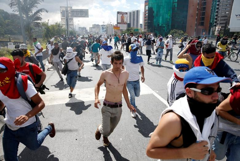 Protesters run after clashes with the police during a rally to demand a referendum to remove Venezuela's President Nicolas Maduro in Caracas, Venezuela, September 1, 2016. REUTERS/Carlos Garcia Rawlins