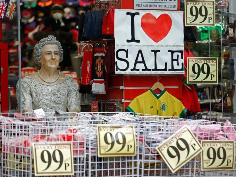 A mannequin of Britain's Queen Elizabeth is displayed by a sale sign in a shop window, in the run-up to Christmas, in central London December 23, 2014. REUTERS/Luke MacGregor