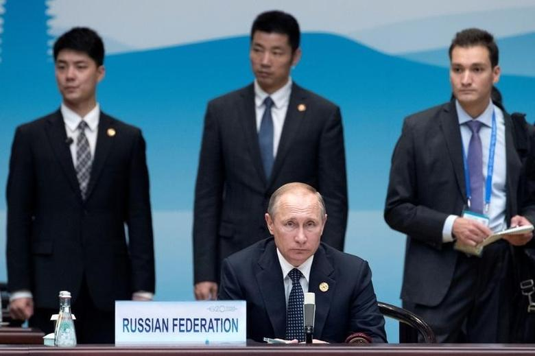 Russian President Vladimir Putin (C) sits before the start of the opening ceremony of the G20 Summit in Hangzhou in eastern China's Zhejiang province, Sunday, Sept. 4, 2016. REUTERS/Mark Schiefelbein/Pool