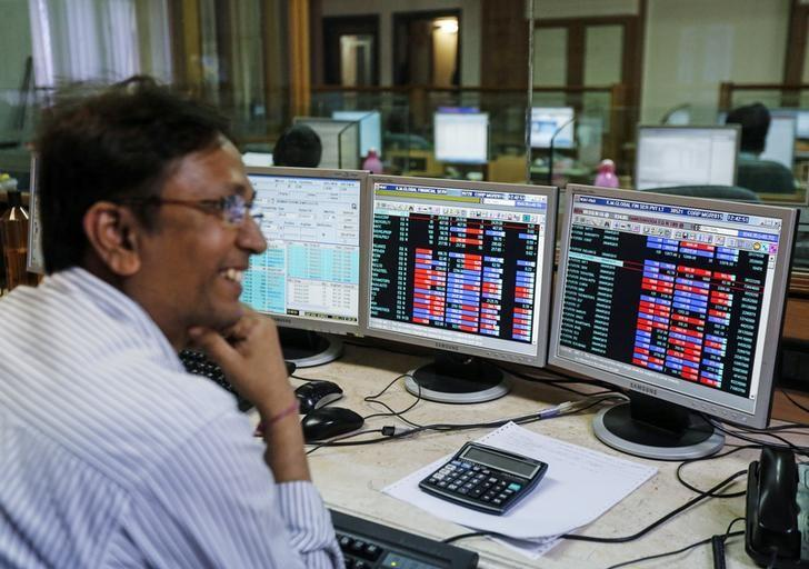 A broker laughs while speaking to a colleague, as they trade on their computer terminals at a stock brokerage firm in Mumbai, March 4, 2015. REUTERS/Shailesh Andrade/Files