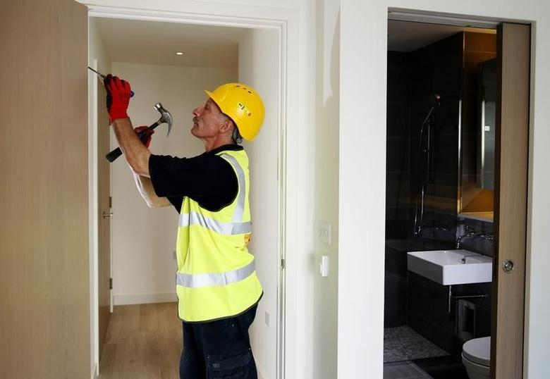 Carpenter Richard Helad adjusts a door in a new apartment constructed by Berkeley Homes in Hackney, northeast London July 22, 2014.    REUTERS/Luke MacGregor