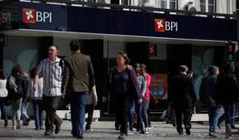 La junta de accionistas del portugués Banco BPI en la que se iba a votar levantar el límite del 20 por ciento a los derechos de voto fue suspendida por segunda vez debido a escollos legales, frustrando aún más la oferta de adquisición lanzada por Caixabank. En la imagen, varias personas pasan junto a una sucursal del banco portugués BPI en Lisboa, el 28 de abril de 2016.  REUTERS/Rafael Marchante