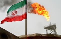 """Una bandera de Irán cerca de una plataforma petrolera, en el Golfo. 25 de julio de 2005. Irán está """"más cerca de la idea"""" de congelar los niveles de producción de petróleo que cuando los ministros de la OPEP se reunieron en junio, dijo el director de asuntos internacionales de la petrolera estatal iraní NIOC, Mohsen Ghamsari, según la organización de medios Argus Media. REUTERS/Raheb Homavandi/File Photo"""