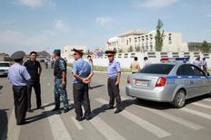 Следователи и милиция у посольства Китая в Бишкеке 30 августа 2016 года. Киргизские силовики во вторник возложили ответственность за атаку смертника на китайское посольство в столице на уйгурских боевиков, воюющих в Сирии. REUTERS/Vladimir Pirogov
