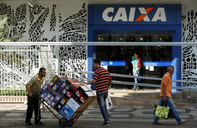 People walk past a Caixa Economica Federal bank in downtown Rio de Janeiro August 20, 2014. REUTERS/Pilar Olivares