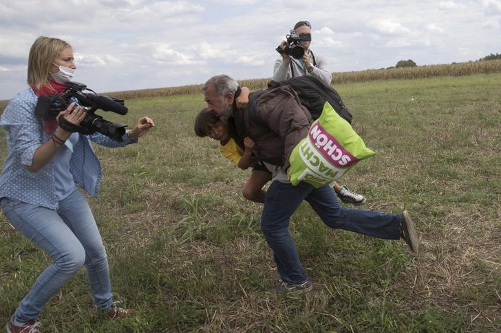 A migrant runs with a child before tripping on TV camerawoman Petra Laszlo (L) and falling as he tries to escape from a collection point in Roszke village, Hungary, September 8, 2015.  REUTERS/Marko Djurica