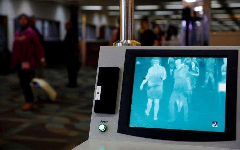 Airline passengers walk past a thermal scanner for body temperature shortly after landing from Singapore at Soekarno-Hatta airport in Jakarta, Indonesia August 30, 2016. REUTERS/Beawiharta