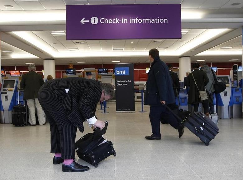 Passengers walk with their luggage at Edinburgh airport in Scotland April 23, 2012.      REUTERS/David Moir