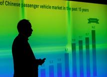 Hubertus Troska, chairman and chief executive officer of Daimler Greater China, is silhouetted against a screen showing a graph of Chinese passenger vehicle market in the past 15 years, as he speaks to reporters at the opening ceremony of the company's Mercedes-Benz research and development (R&D) centre in Beijing November 3, 2014. REUTERS/Kim Kyung-Hoon/File Photo