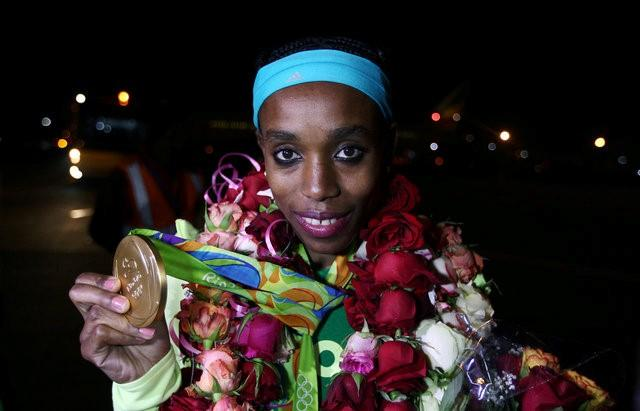 Almaz Ayana, who won the gold medal for the women 10,000m at the Rio Olympics, displays her medal for photographers upon her arrival at the Bole International Airport in Ethiopia's capital Addis Ababa August 23, 2016. Picture taken August 23, 2016. REUTERS/Tiksa Negeri