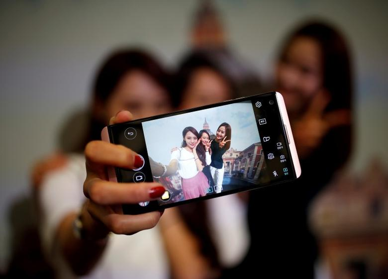 Models pose for photographs with a LG electronics' new V20 premium smartphone during its unveiling ceremony in Seoul, South Korea, September 7, 2016. REUTERS/Kim Hong-Ji
