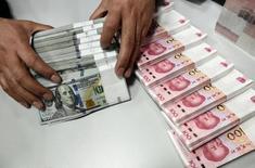 Un empleado cuenta fajos de billetes de dólares estadounidenses y yuanes chinos, en una sucursal del Banco de China, en Taiyuan, Shanxi, China. 4 de enero de 2016. Las reservas de divisas de China se redujeron en agosto a 3,19 billones de dólares, mostraron el miércoles datos del banco central, en línea con las expectativas del mercado y a su nivel más bajo desde diciembre del 2011. REUTERS/Jon Woo