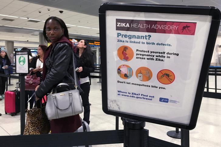 A woman looks at a Center for Disease Control (CDC) health advisory sign about the dangers of the Zika virus as she lines up for a security screening at Miami International Airport in Miami, Florida, U.S., May 23, 2016.  REUTERS/Carlo Allegri