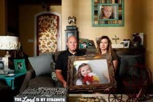 Kelly and Ryan Breaux sit holding a portrait of their deceased daughter Emma Breaux  in their home in Breaux Bridge, Louisiana, on June 16, 2016.  REUTERS/Edmund Fountain/Files