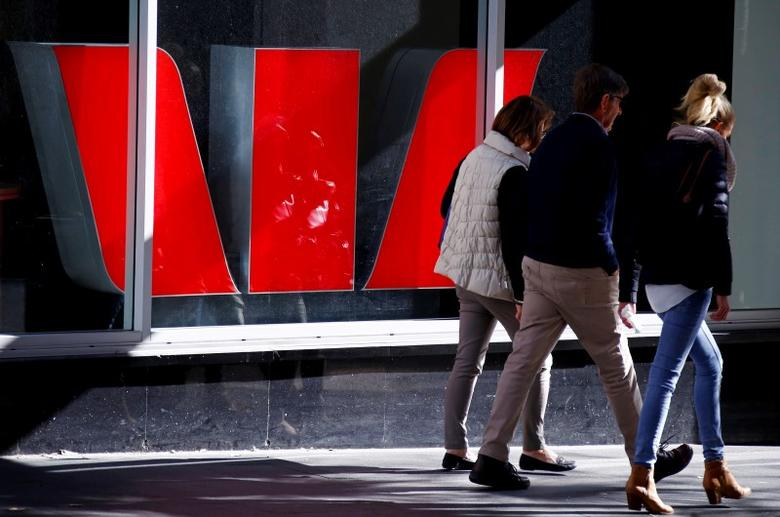 Pedestrians walk past a logo of the Westpac Bank Corp on display in a window of a branch located in central Sydney, Australia, July 2, 2016. REUTERS/David Gray