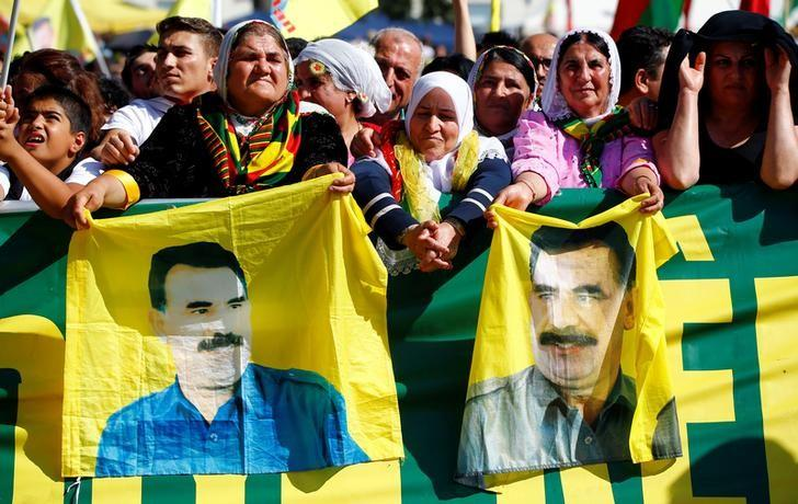 Traditionally dressed Kurdish women hold flags showing jailed PKK leader (Kurdistan Workers' Party) Abdullah Ocalan during a rally of some 30,000 Kurdish Turks against Turkish President and AKP party leader Recep Tayyip Erdogan in Cologne, Germany September 3, 2016. REUTERS/Wolfgang Rattay