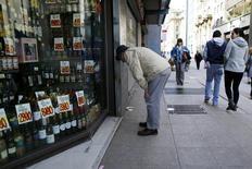Una persona mira los precios de los productos desde fuera de una tienda en el centro de Santiago. 26 de agosto de 2016. El Índice de Precios al Consumidor (IPC) en Chile registró una nula variación en agosto, en línea con lo esperado, ante una debilitada demanda interna y menores efectos cambiarios, lo que contribuyó también a una disminución de la inflación anualizada. REUTERS/Ivan Alvarado