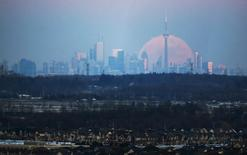 The moon rises over the Toronto city skyline as seen from Milton, Ontario, Canada, January 23, 2016.    REUTERS/Mark Blinch