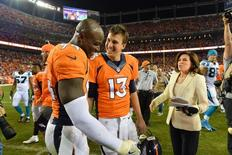 Sep 8, 2016; Denver, CO, USA; Denver Broncos outside linebacker DeMarcus Ware (94) and quarterback Trevor Siemian (13) celebrate the win against the Carolina Panthers at Sports Authority Field at Mile High. The Broncos defeated the Panthers 21-20. Mandatory Credit: Ron Chenoy-USA TODAY Sports