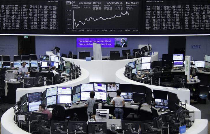Traders work at their desks in front of the German share price index, DAX board, at the stock exchange in Frankfurt, Germany, September 7, 2016. REUTERS/Staff/Remote/Files