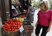 Una mujer mira los precios de los vegetales en una tienda en Buenos Aires, Argentina. 30 de enero de 2014.  Los precios minoristas de Argentina habrían subido un 0,8 por ciento promedio en agosto, acercándose a los deseos del Gobierno, avalados en gran parte a la decisión judicial de retrotraer tarifas de servicios, según un sondeo de Reuters publicado el viernes. REUTERS/Stringer