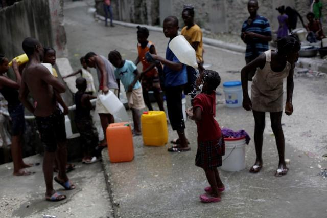 A girl cools off with drinkable water at a source in Port-au-Prince, Haiti, September 7, 2016. REUTERS/Andres Martinez Casares