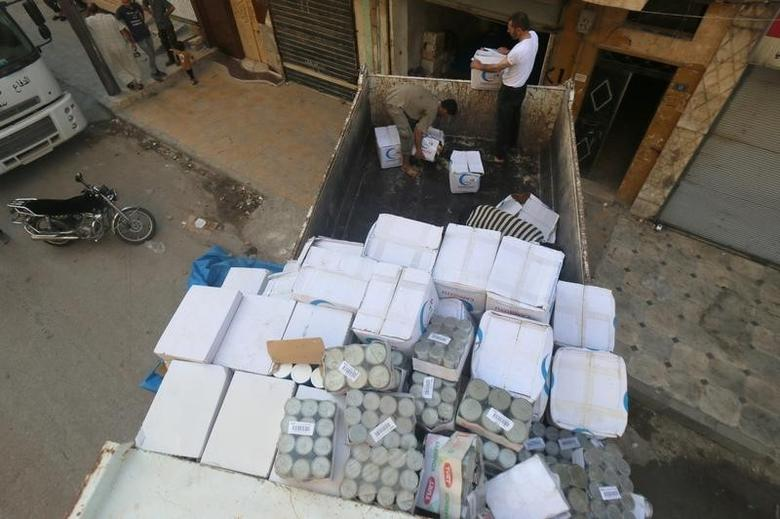 FILE PHOTO: Workers unload food aid parcels that were brought into rebel held areas of Aleppo through civil defence vehicles from a newly opened corridor that linked besieged opposition held eastern Aleppo with western Syria that was captured recently by rebels, in Aleppo August 12, 2016. REUTERS/Abdalrhman Ismail