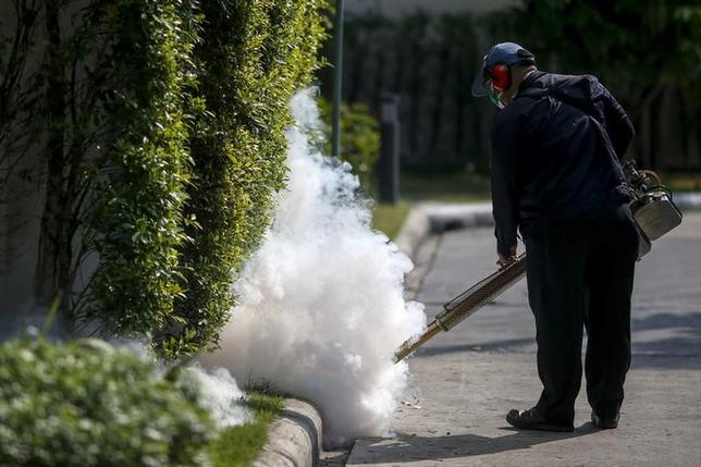 A worker sprays insecticide for mosquitos at a village in Bangkok, Thailand, January 13, 2016. REUTERS/Athit Perawongmetha
