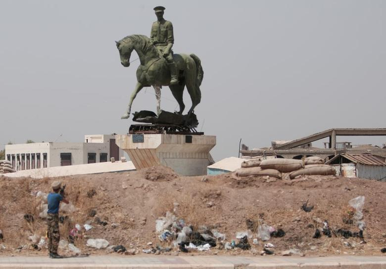 A Kurdish fighter from the People's Protection Units (YPG) fires his weapon at a statue of Bassel al-Assad, brother of Syria's President Bashar, in the Ghwairan neighborhood of Hasaka, Syria, August 22, 2016.REUTERS/Rodi Said
