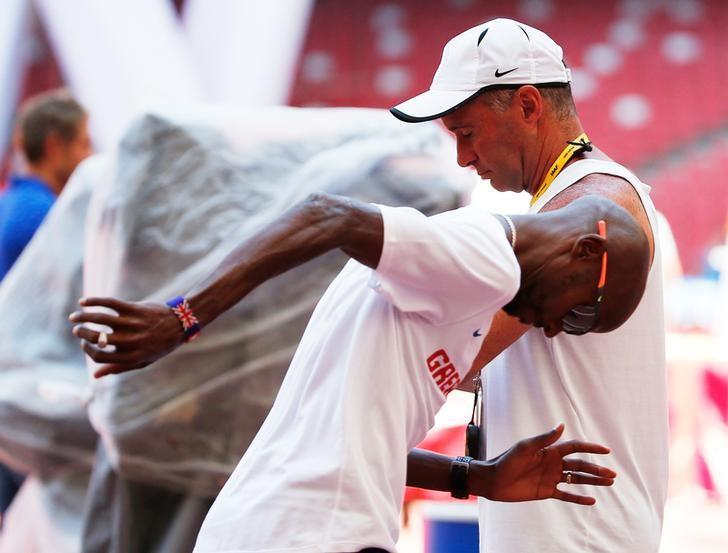 Mo Farah of Great Britain jobs past coach Alberto Salazar in the Bird's Nest Stadium at the Wold Athletics Championships in Beijing, China, August 21, 2015.  REUTERS/Lucy Nicholson/Files