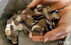 Кассир пересчитывает рублевые монеты в Красноярске. Федеральный бюджет РФ в январе-августе был исполнен с дефицитом 1,52 триллиона рублей, или 2,9 процента ВВП, сообщило министерство финансов.  REUTERS/Ilya Naymushin/File Photo