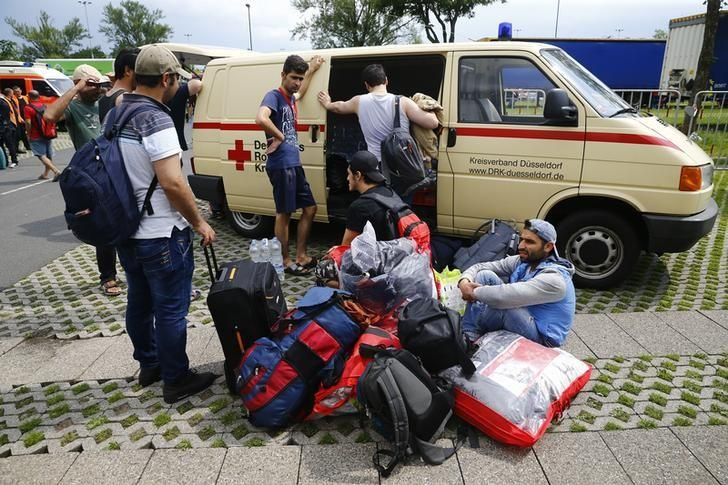 Migrants rest on the ground after exhibition halls used as refugee camps were damaged in a fire in Duesseldof, Germany, June 7, 2016.      REUTERS/Wolfgang Rattay/File Photo