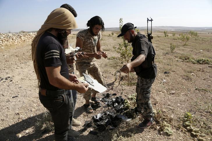 Rebel fighters from the Ahrar al-Sham Movement inspect a site as they gather pieces of the wreckage of an unidentified and unmanned aircraft that had crashed at their base in Maarchmarein village in the southern part of Idlib province, Syria October 20, 2015. REUTERS/Khalil Ashawi/File Photo