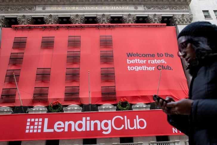 A woman looks at her phone as she passes by a Lending Club banner on the facade of the the New York Stock Exchange December 11, 2014.   REUTERS/Brendan McDermid/File Photo