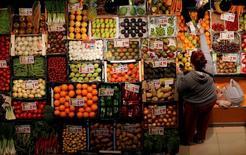 La moderación en las caídas de la inflación en España continuó en agosto, con el Índice de Precios al Consumo (IPC) bajando un 0,1 por ciento en tasa anual, según el dato definitivo del INE, que coincide con la lectura preliminar. En la imagen, una mujer compra frutas y verduras en un mercado de Sevilla, el  7 de marzo de 2016. REUTERS/Marcelo del Pozo/File Photo