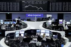 Traders work at their desks in front of the German share price index, DAX board, at the stock exchange in Frankfurt, Germany, September 9, 2016. REUTERS/Staff/Remote