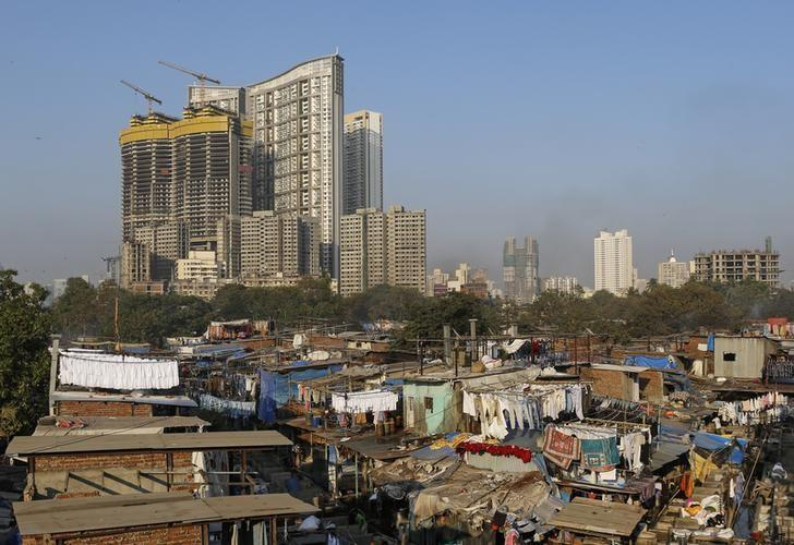 High-rise residential buildings are seen behind a cluster of hutments at an open laundry in Mumbai, India, January 18, 2016. REUTERS/Danish Siddiqui/File Photo