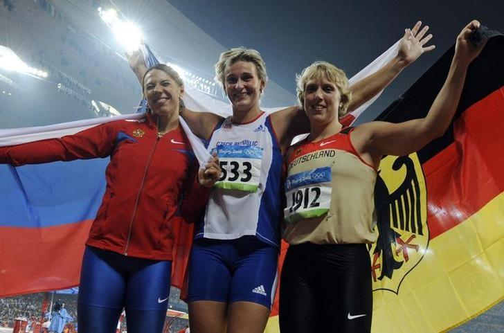 Women's javelin throw winner Barbora Spotakova of the Czech Republic (C) celebrates with second classified Maria Abakumova of Russia and third classified Christina Obergfoll of Germany after the athletics competition in the National Stadium at the Beijing 2008 Olympic Games August 21, 2008.     REUTERS/Wolfgang Rattay/File Photo