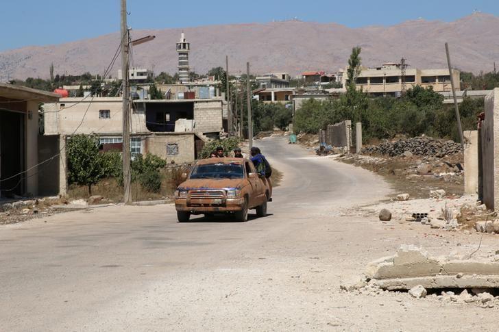 Rebel fighters ride a vehicle in Jubata al-Khashab, in Quneitra countryside, Syria September 11, 2016. REUTERS/Alaa Al-Faqir