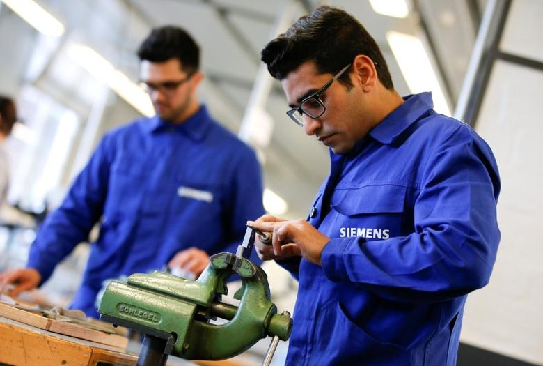 Refugees show their skills in metal processing works during a media tour at a workshop for refugees organized by German industrial group Siemens in Berlin, Germany, April 21, 2016. REUTERS/Fabrizio Bensch/File Photo