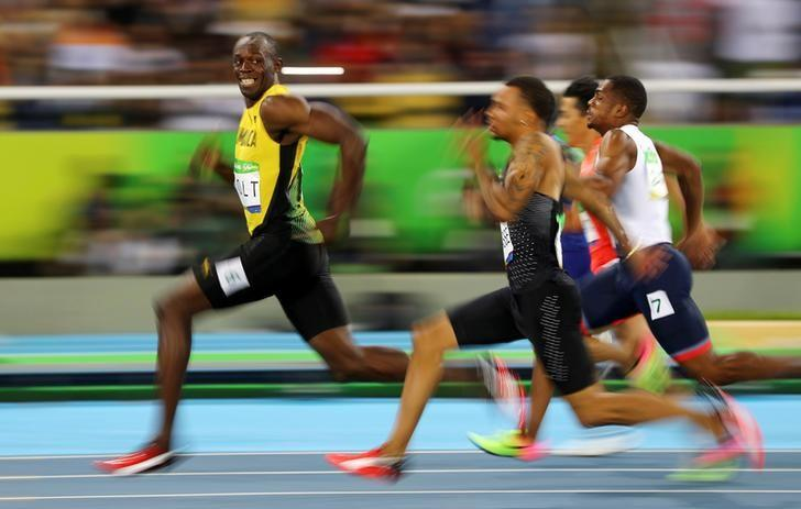 Usain Bolt (JAM) of Jamaica looks at Andre De Grasse (CAN) of Canada as they compete.  REUTERS/Kai Pfaffenbach