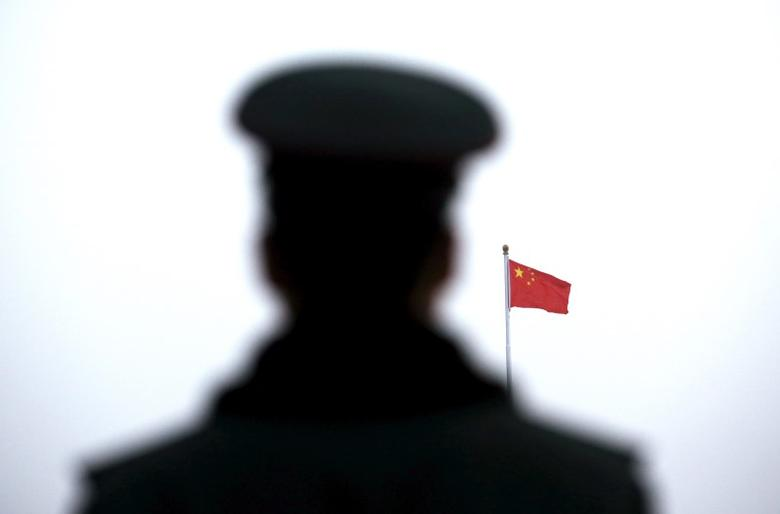 A paramilitary policeman watches a flag-raising ceremony at Tiananmen Square ahead of the opening session of the National People's Congress (NPC) in Beijing, China, March 5, 2016. REUTERS/Kim Kyung-hoon