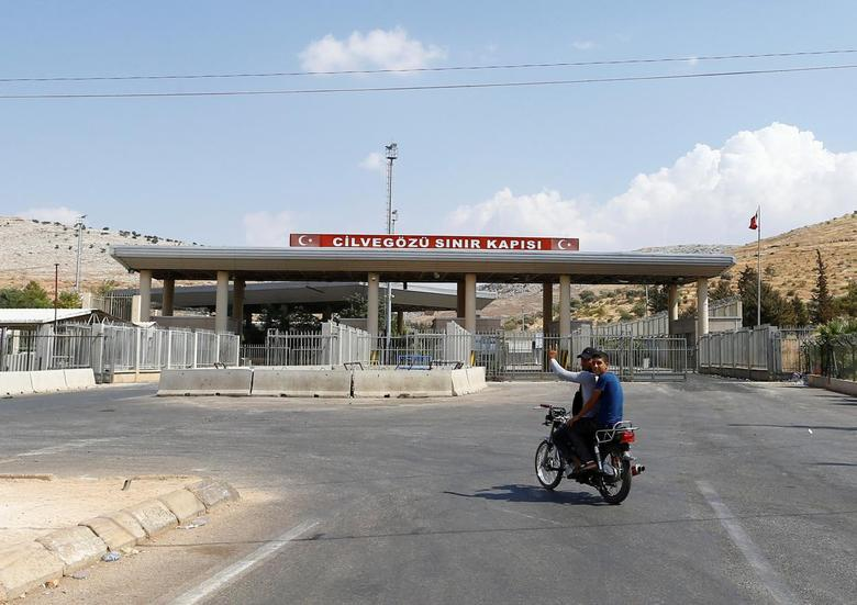 A Syrian man rides a motorcycle at the Turkish Cilvegozu border gate, located opposite the Syrian commercial crossing point Bab al-Hawa, in Reyhanli, Hatay province, Turkey, September 14, 2016. REUTERS/Osman Orsal