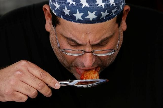 Competitive eater Ed Jarvis uses a spoon to eat during a meatball eating contest in New York, U.S., September 14, 2016.  REUTERS/Lucas Jackson
