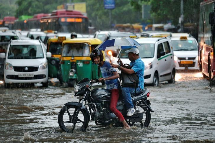 A man rides his motorcycle through a flooded road during monsoon rains in New Delhi, India August 31, 2016. REUTERS/Cathal McNaughton